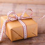 Geschenk mit Schleife auf Holz